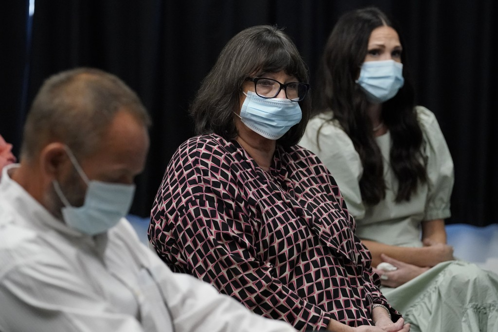 Megan Tobey, center, the sister of murder victim Paul Howell, sits with family members during a commutation hearing for his convicted killer, Julius J...