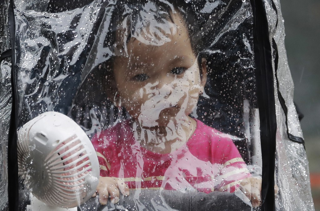 A baby looks out through the raindrop canopy in a rain caused by Typhoon Chanthu in Taipei, Taiwan, Sunday, Sept. 12, 2021. Typhoon Chanthu drenched T...