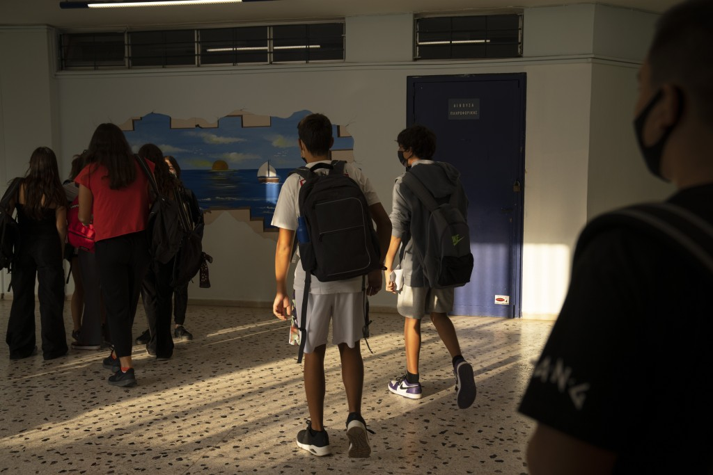 Students walk in the corridor of a junior high school in Athens, Monday, Sept. 13, 2021. Public and private sector employees will have to pay for week...