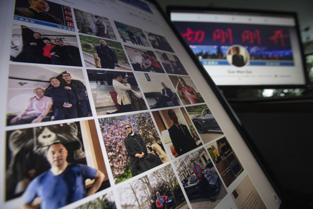 FILE - In this Aug. 21, 2020, file photo, Facebook pages from self-exiled Chinese tycoon Guo Wengui's account are seen on computer screens in Beijing....