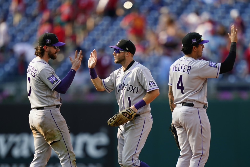 Colorado Rockies' Brendan Rodgers, from left, Garrett Hampson and Colton Welker celebrate after a baseball game against the Philadelphia Phillies, Sun...