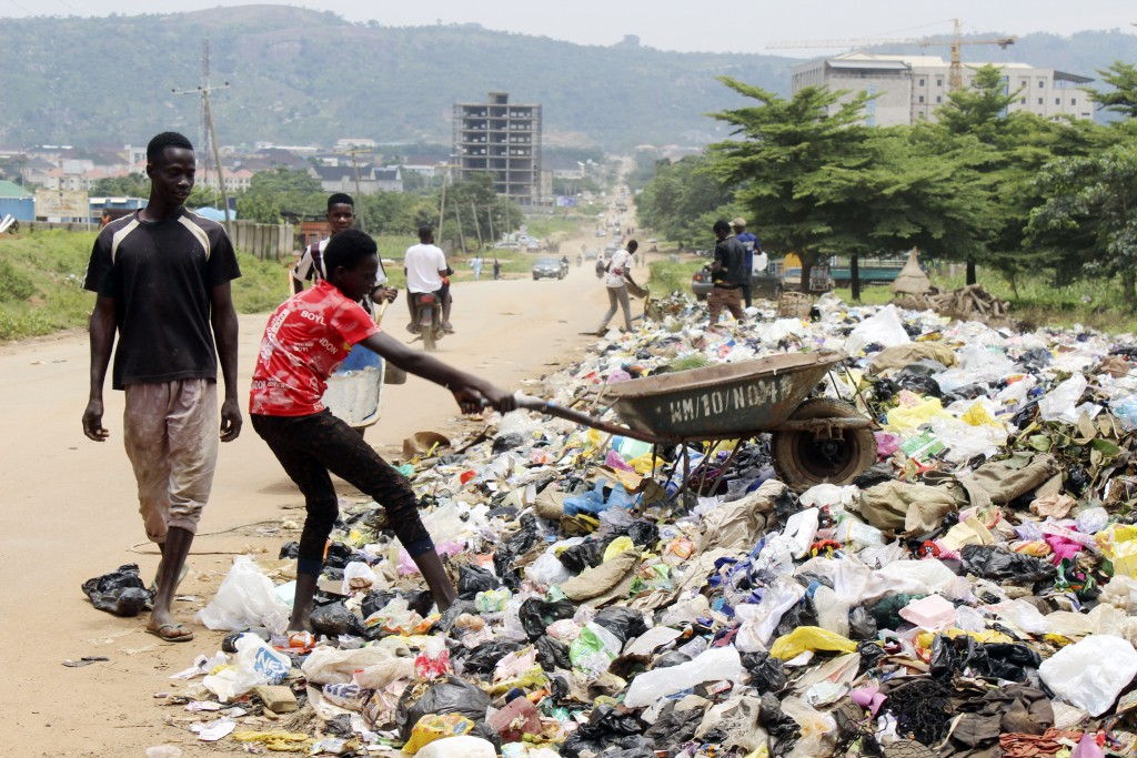 A boy empties garbage onto the street in Abuja, Nigeria, Friday, Sept. 3, 2021. Nigeria is seeing one of its worst cholera outbreaks in years, with mo...