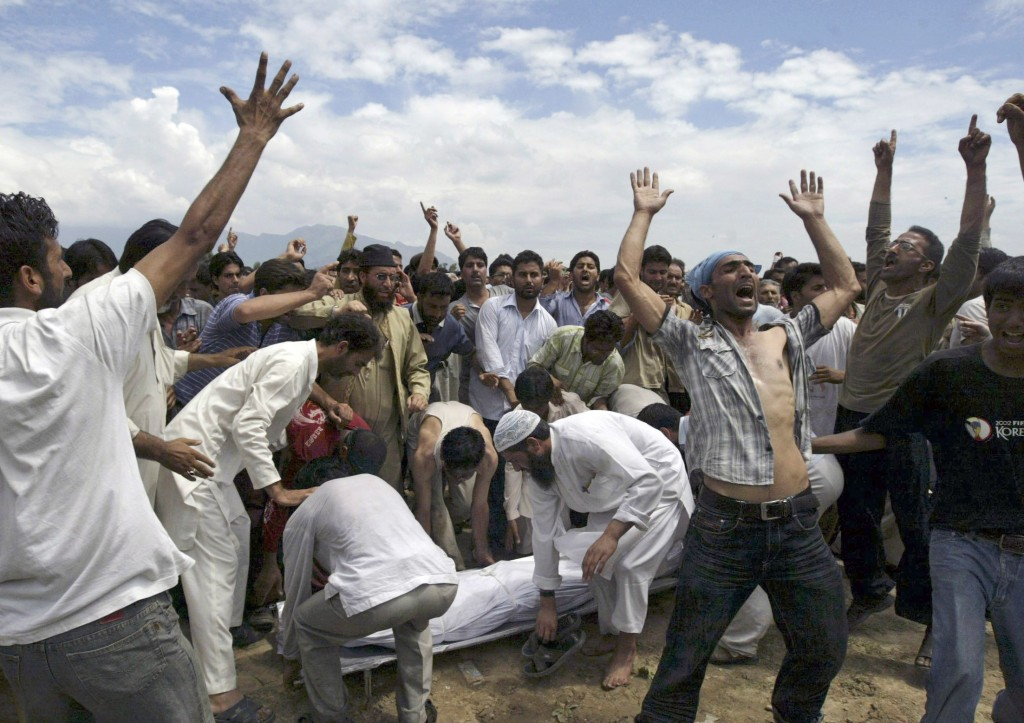 FILE - In this Aug. 14, 2008, file photo, Kashmiri Muslims shout slogans demanding independence from India as others prepare to carry the body of a ma...