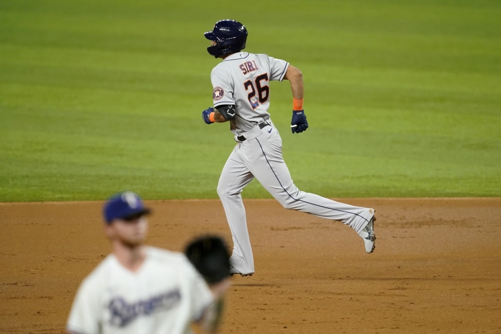 Houston Astros' Jose Siri rounds the bases after hitting a two-run home run off of Texas Rangers starting pitcher A.J. Alexy, front, in the third inni...