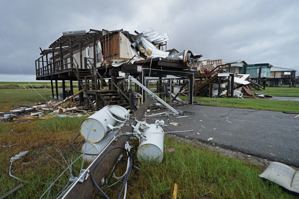 Storm clouds from approaching Tropical Storm Nicholas are seen behind homes destroyed by Hurricane Ida, in Pointe-aux-Chenes, La., Tuesday, Sept. 14, ...