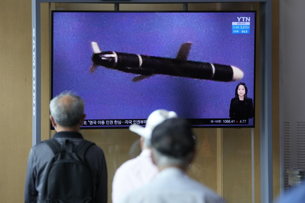 """People watch a TV screen showing a news program showing a North Korean handout photo that says, """"North Korea's long-range cruise missiles tests,"""" in S..."""