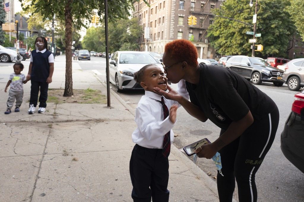 A mother gives her son a kiss as he arrives for the first day of class at Brooklyn's PS 245 elementary school, Monday, Sept. 13, 2021, in New York. Cl...