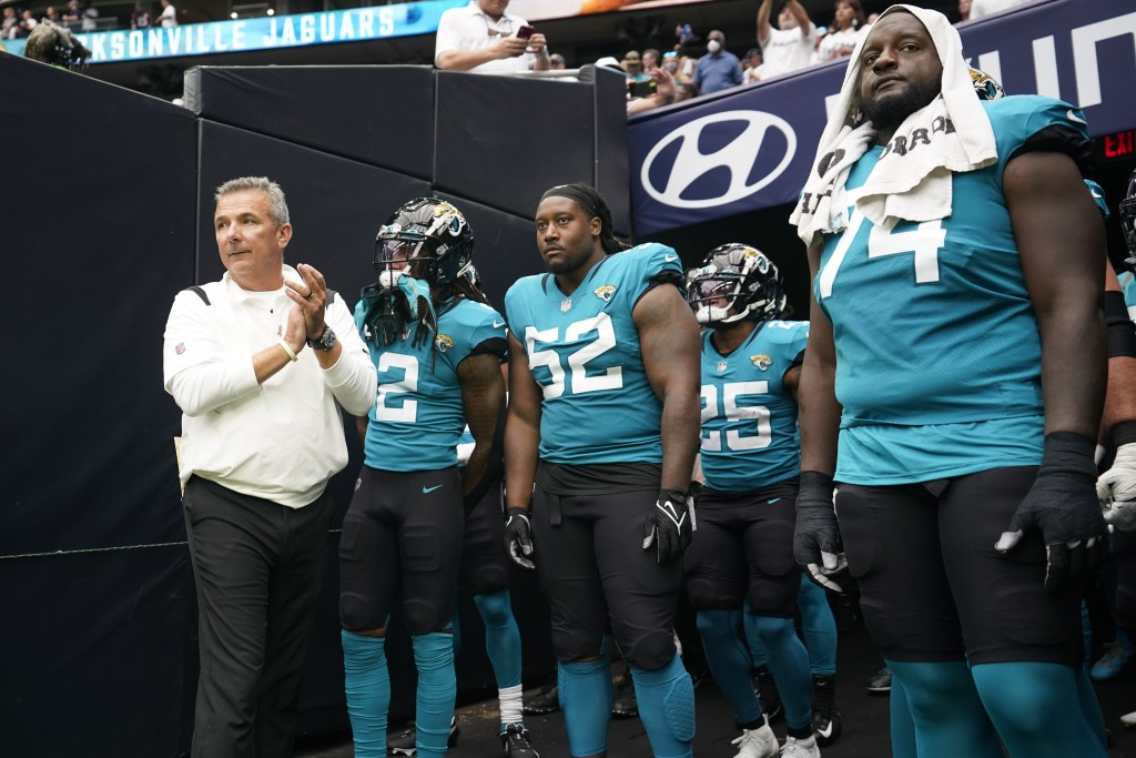 Jacksonville Jaguars coach Urban Meyer, left, prepares to lead his team onto the field before an NFL football game against the Houston Texans Sunday, ...