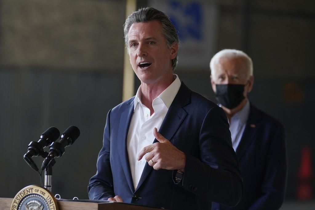 President Joe Biden listens as California Gov. Gavin Newsom speaks about recent wildfires, at Sacramento Mather Airport, Monday, Sept. 13, 2021, in Ma...