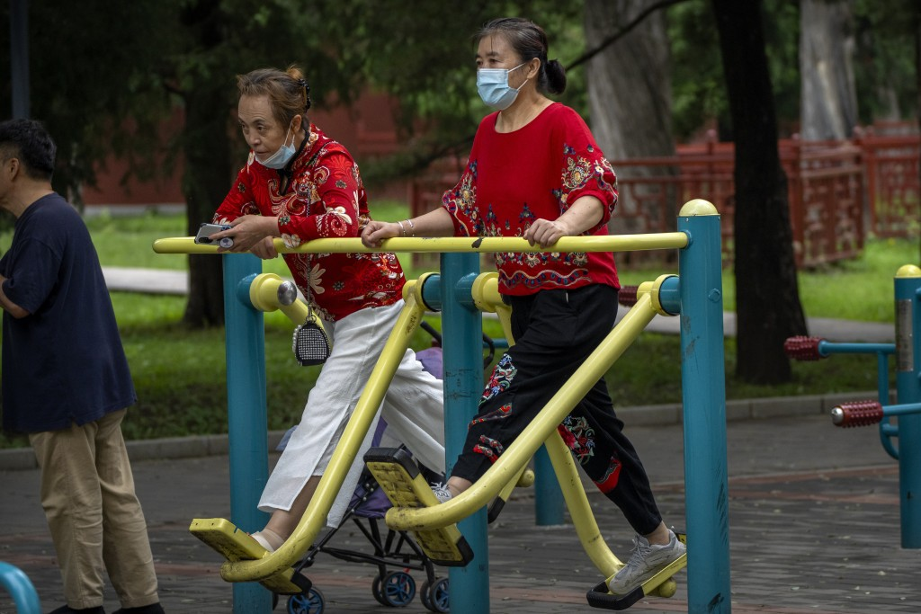 A woman wearing a face mask to protect against COVID-19 uses an exercise machine at a public park in Beijing, Thursday, Sept. 9, 2021. (AP Photo/Mark ...