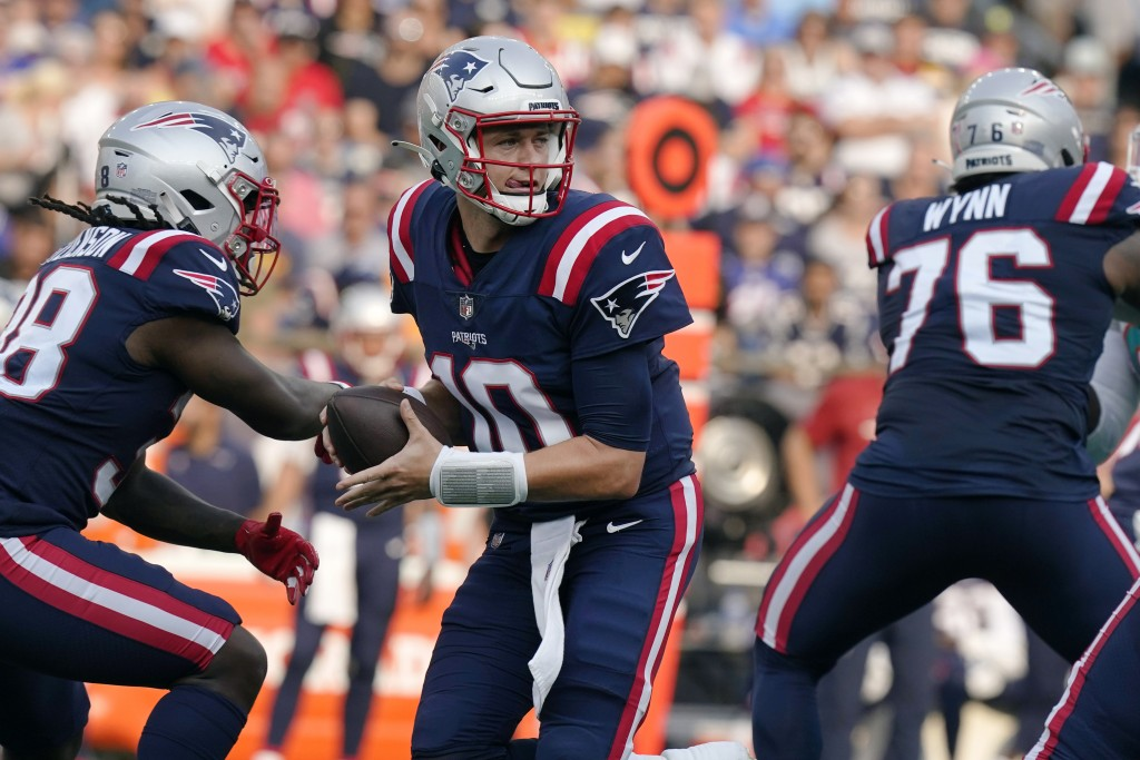 New England Patriots quarterback Mac Jones (10) looks to pass after faking a hand off during the first half of an NFL football game against the Miami ...