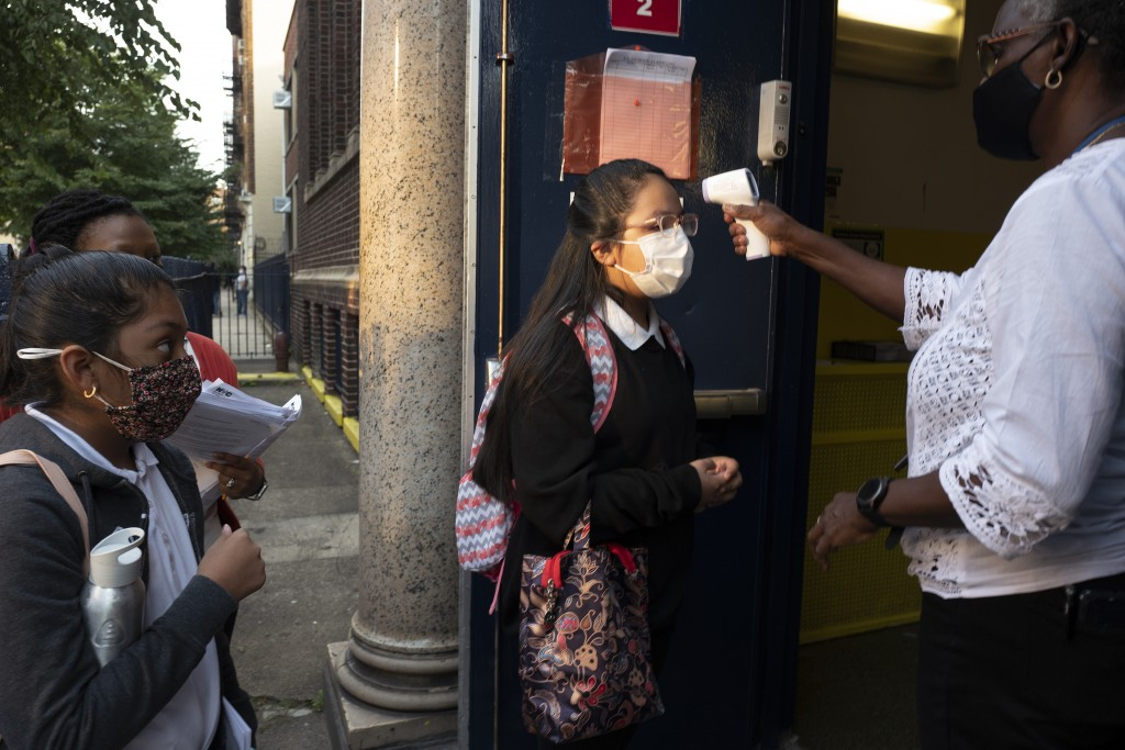 A girl has her temperature checked as she arrives for the first day of school at Brooklyn's PS 245 elementary school, Monday, Sept. 13, 2021, in New Y...