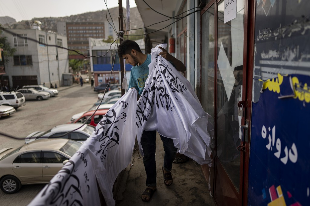A worker collects newly hand printed Taliban flags in a workshop in Kabul's Jawid market, Afghanistan, Sunday, Sept. 12, 2021. The small flag shop, tu...