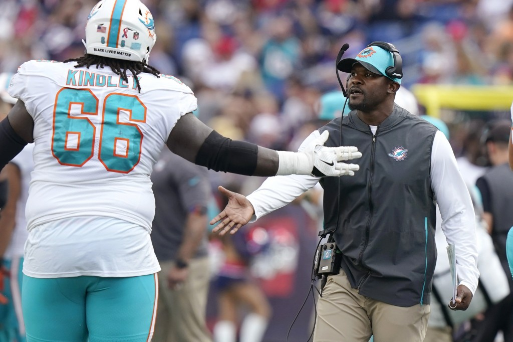 Miami Dolphins head coach Brian Flores, right, congratulates offensive guard Solomon Kindley (66) during the first half of an NFL football game agains...