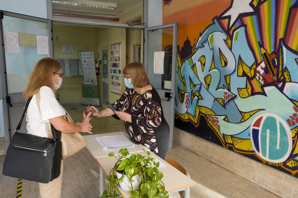 """A teacher, left, has her so-called """"Green Pass"""" checked by a school worker as she arrives at the """"Isacco Newton"""" high school, in Rome, Monday, Sept. 1..."""