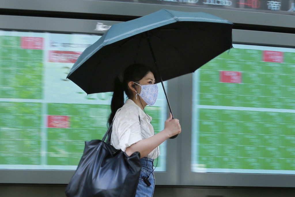 A woman walks by an electronic stock board of a securities firm in Tokyo, Wednesday, Sept. 15, 2021. Asian stock markets followed Wall Street down on ...