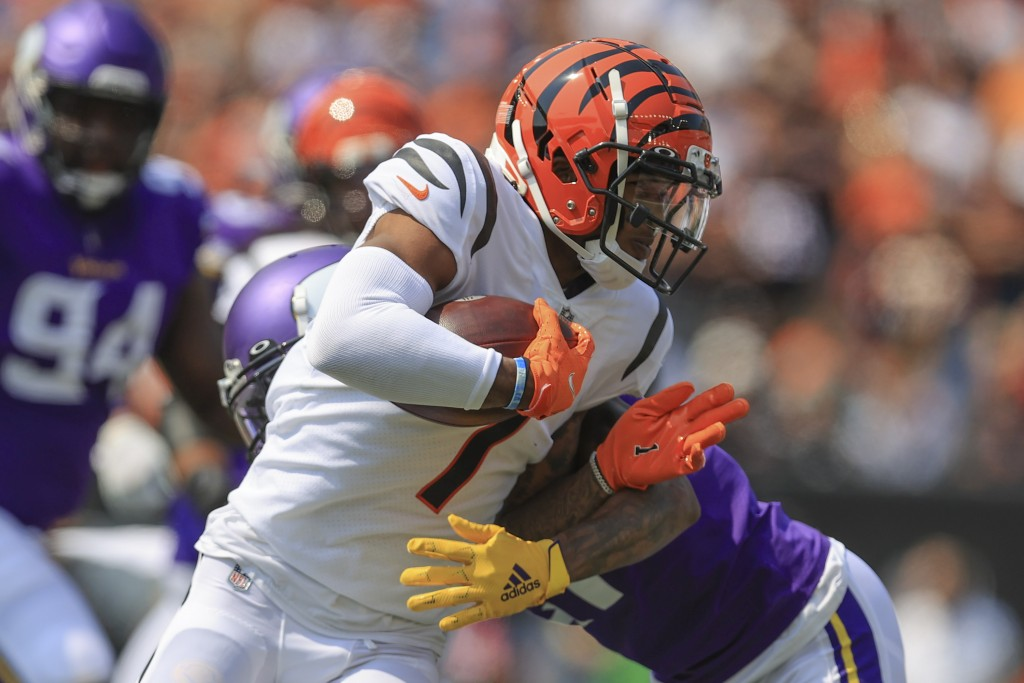 Cincinnati Bengals wide receiver Ja'Marr Chase (1) runs as Minnesota Vikings defensive back Bashaud Breeland tries to tackle him in the first half of ...