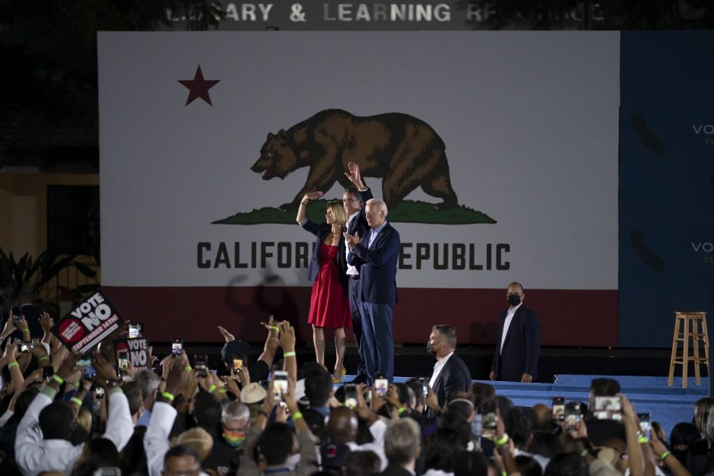 President Joe Biden, from right, California Gov. Gavin Newsom, and wife, Jennifer Siebel Newsom, acknowledge supporters at a rally ahead of the Califo...