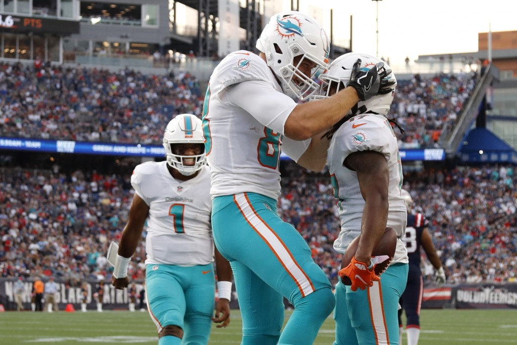 Miami Dolphins wide receiver Jaylen Waddle, right, celebrates with Mike Gesicki after his touchdown during the second half of an NFL football game aga...