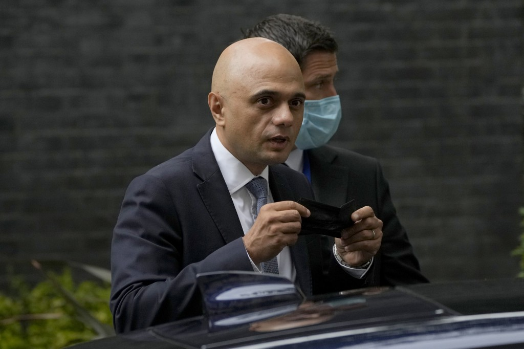 FILE - In this Wednesday, June 30, 2021 file photo, Britain's newly appointed Health Secretary Sajid Javid looks at photographers as he puts on a face...