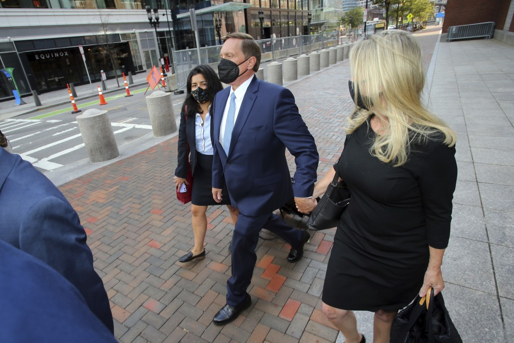 John Wilson, center, holds his wife's hand, right, as he leaves the John Joseph Moakley Federal Courthouse after the first day of his trial in the col...