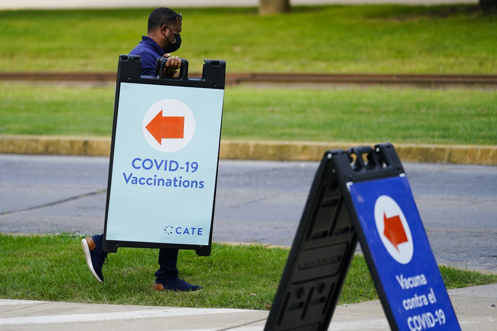 A worker posts placard for a COVID-19 vaccination clinic at the Reading Area Community College in Reading, Pa., Tuesday, Sept. 14, 2021. (AP Photo/Mat...