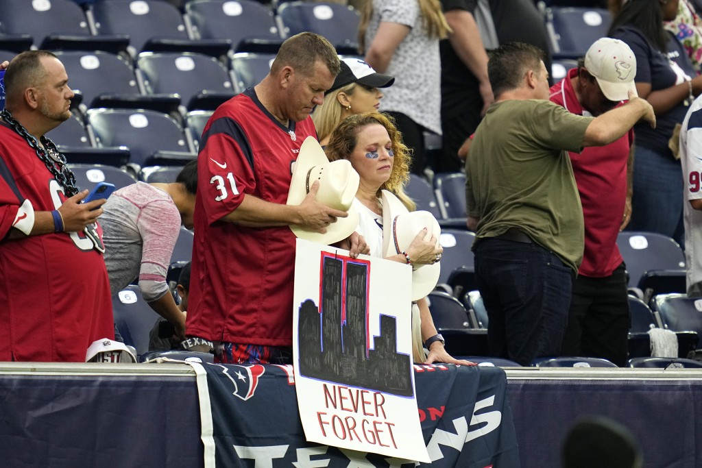 Houston Texans fans bow their heads during a 9/11 memorial video before an NFL football game against the Jacksonville Jaguars Sunday, Sept. 12, 2021, ...
