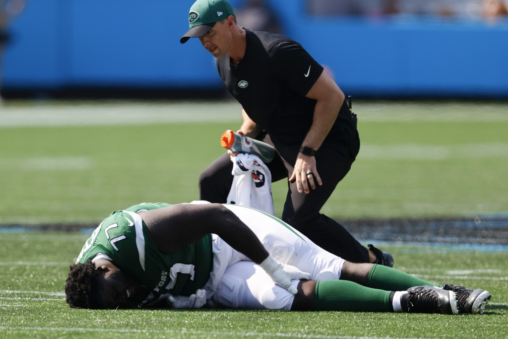 New York Jets offensive tackle Mekhi Becton is helped on the field during the second half of an NFL football game against the Carolina Panthers Sunday...