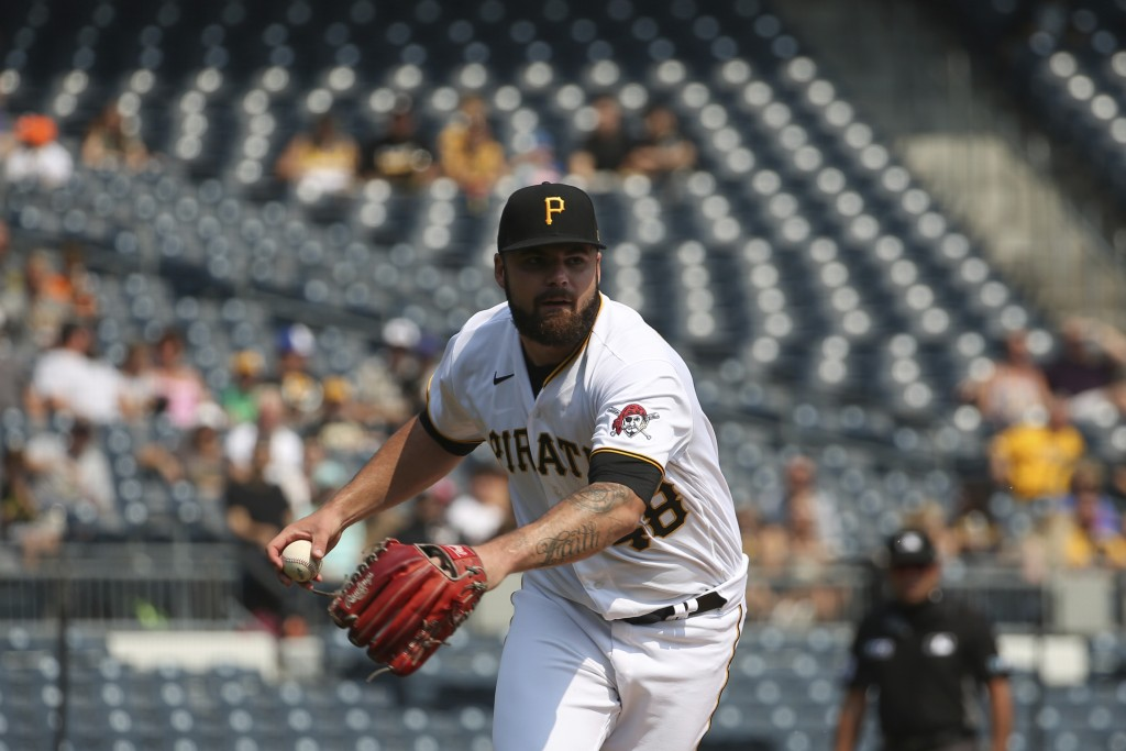 Pittsburgh Pirates starting pitcher Bryse Wilson (48) collects a hit and prepares to throw to first base in the first inning during a baseball game ag...
