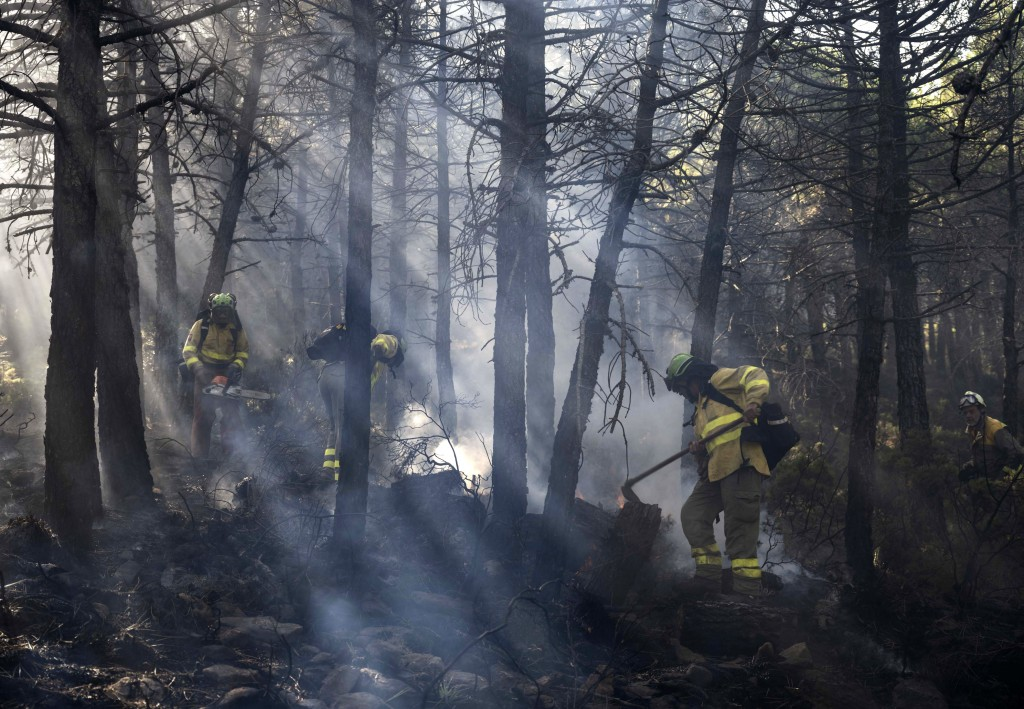 Forest firefighters work on a wildfire near the town of Jubrique, in Malaga province, Spain, Saturday, Sept. 11, 2021. Firefighting crews in southern ...