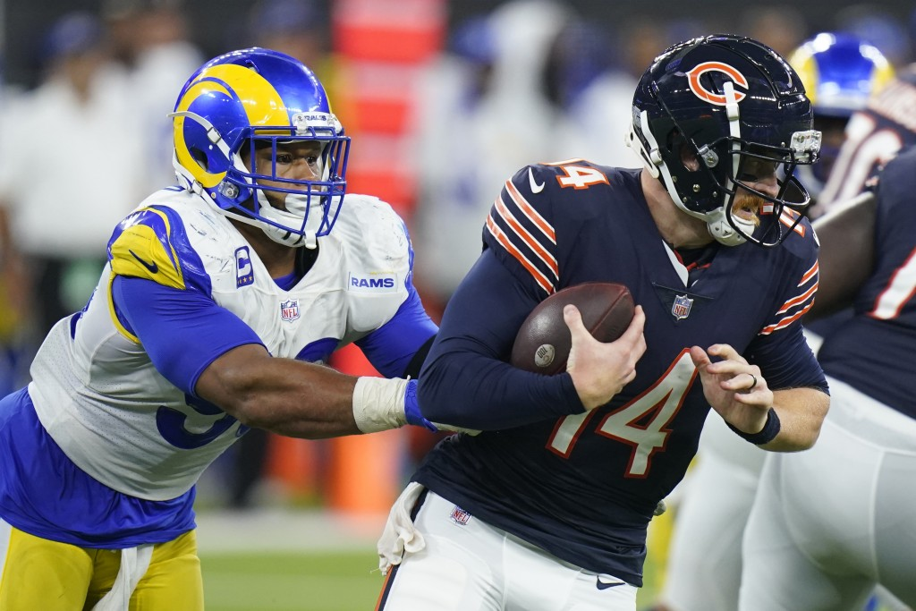 Chicago Bears quarterback Andy Dalton, right, is hauled down by Los Angeles Rams defensive end Aaron Donald during the second half of an NFL football ...