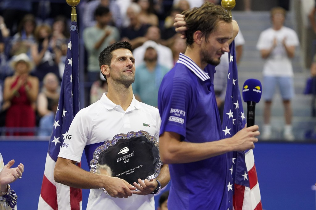 Novak Djokovic, of Serbia, holds the runner-up trophy as Daniil Medvedev, of Russia, prepares to receive the championship trophy after Medvedev defeat...