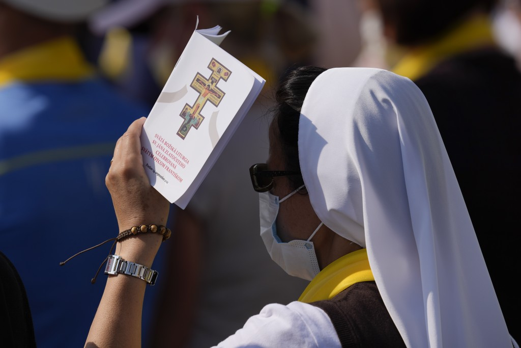 A nun shelters herself from the sun with a prayer booklet during a Byzantine rite Mass celebrated by Pope Francis at Mestska sportova hala Square, in ...