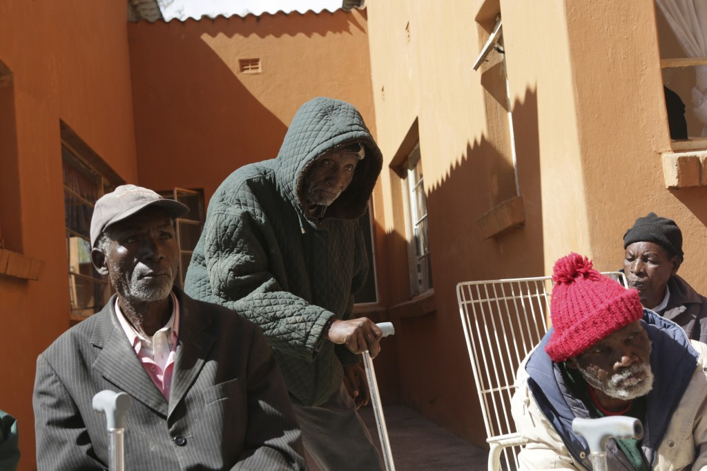 Elderly men gather outside Melfort Old People's home on the outskirts of Harare, Zimbabwe, Sunday, July 25, 2021. The economic ravages of COVID-19 are...