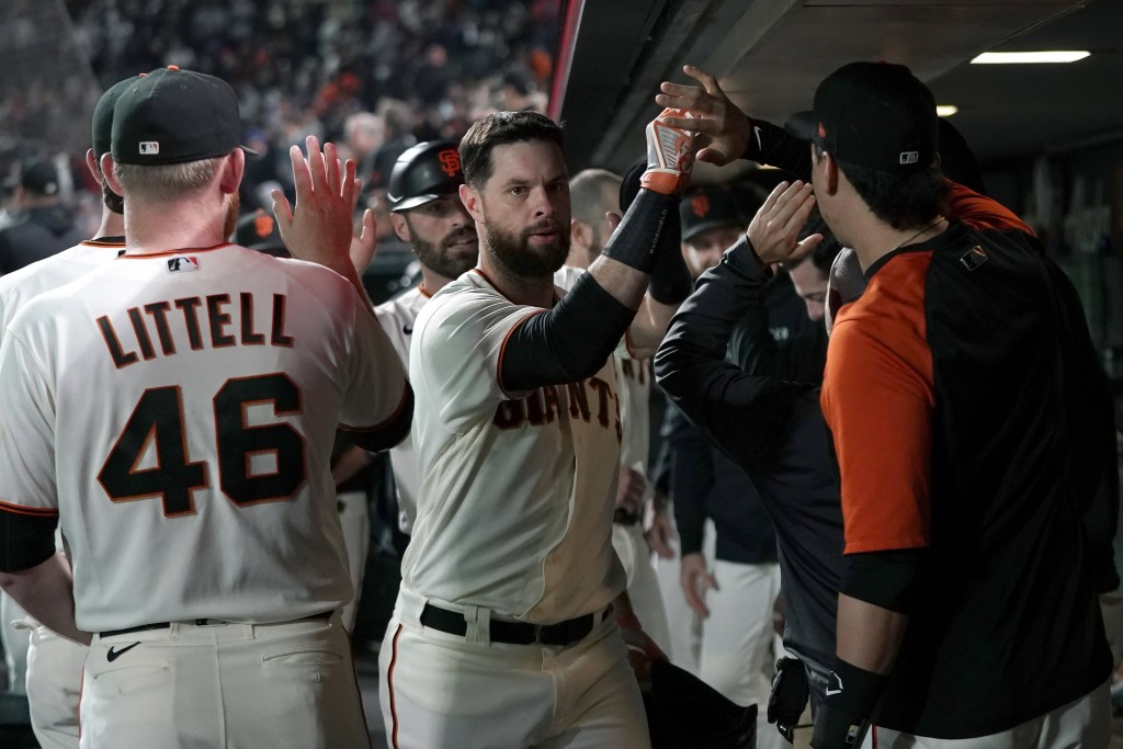 San Francisco Giants' Brandon Belt, middle, is congratulated by teammates after hitting a two-run home run against the San Diego Padres during the fou...