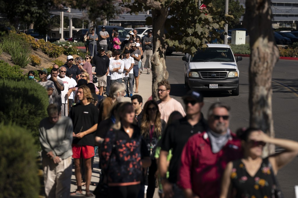 People wait in line to vote outside a vote center Tuesday, Sept. 14, 2021, in Huntington Beach, Calif. With Gov. Gavin Newsom's fate at stake, Califor...