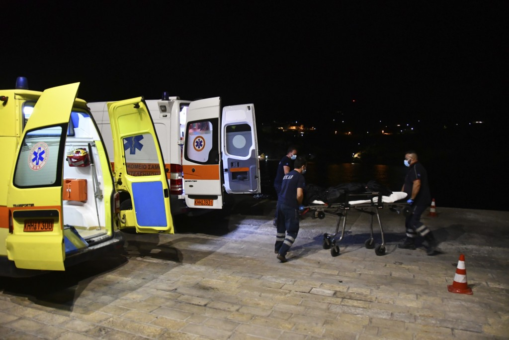 Paramedics wheel a gurney with a body at Pythagorio port, on the eastern Aegean island of Samos, Greece, late Monday, Sept. 13, 2021. Authorities in G...