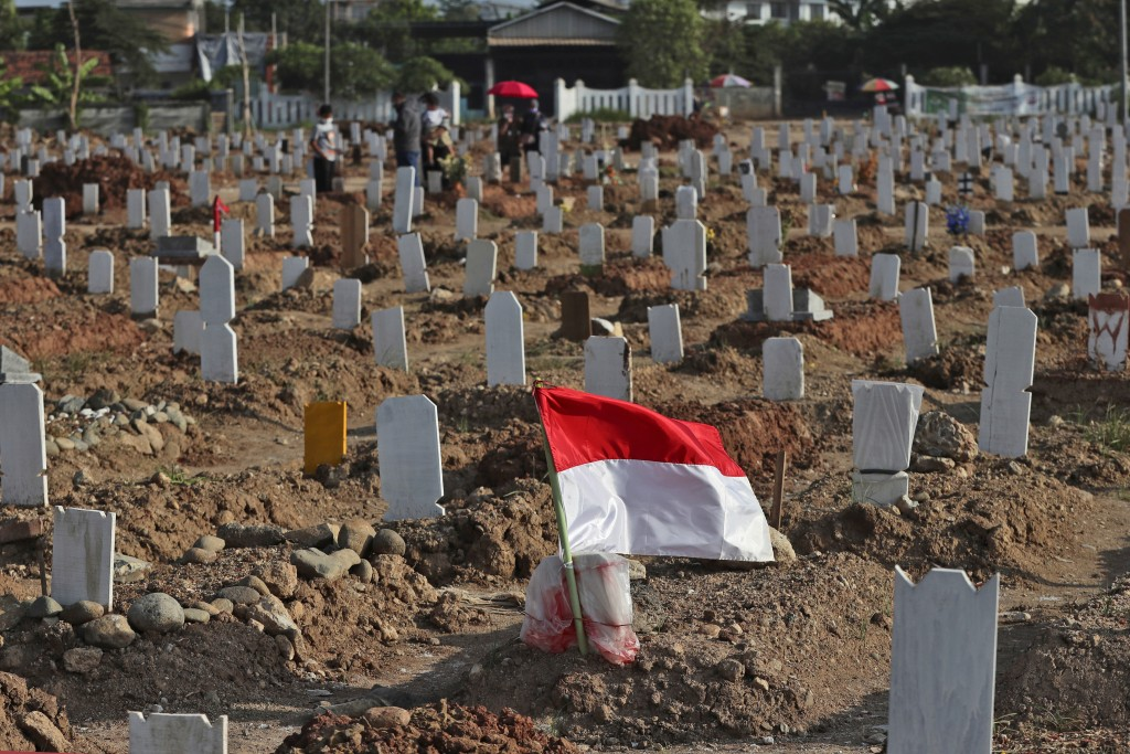An Indonesian national Red-White flag flutters at the grave of a COVID-19 victim at Rorotan Cemetery in Jakarta, Indonesia, Wednesday, Sept. 1, 2021. ...