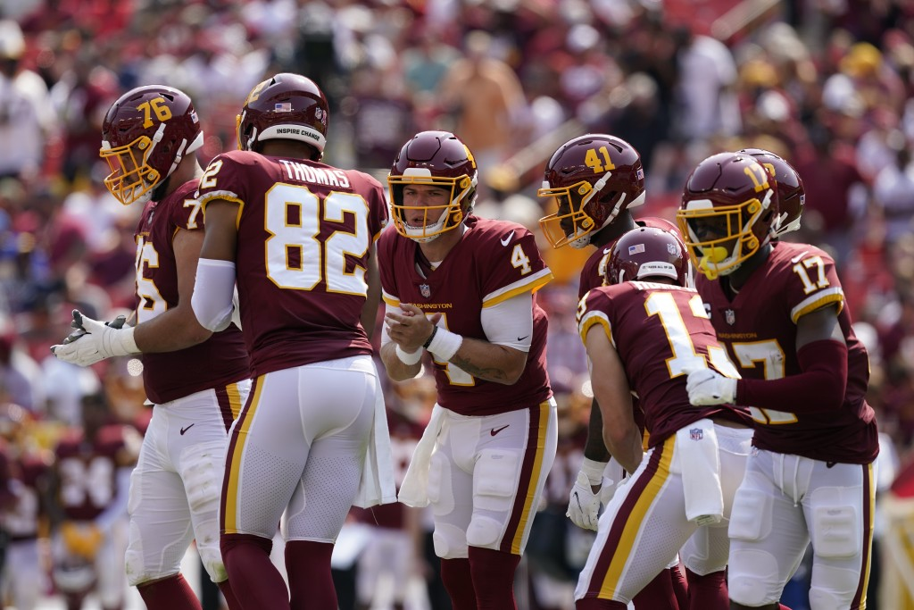 Washington Football Team quarterback Taylor Heinicke (4) in the huddle with teammates during the first half of an NFL football game against the Los An...