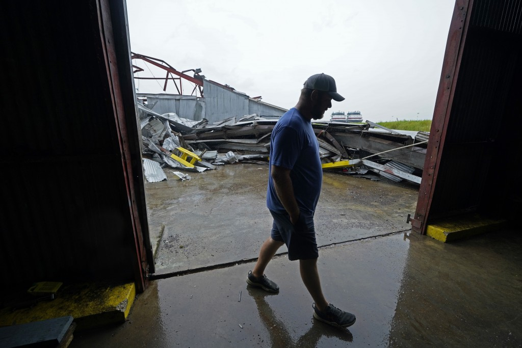 Jarod Voisin walks through damage of his family's heavily damaged oyster processing plant, as rain from Tropical Storm Nicholas, currently in the Gulf...