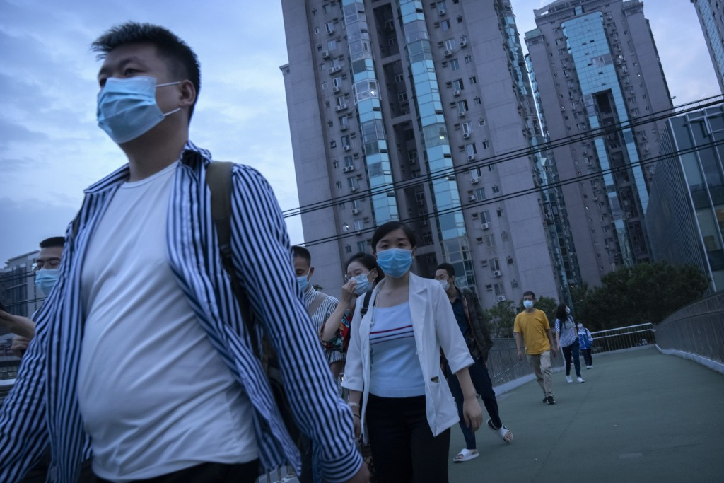 People wearing face masks to protect against COVID-19 walk across a pedestrian bridge near a neighborhood with a suspected coronavirus case in Beijing...