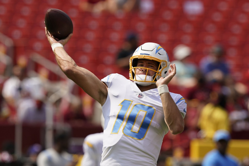 Los Angeles Chargers quarterback Justin Herbert (10) throws during pregame warmups prior to the start of an NFL football game against the Washington F...