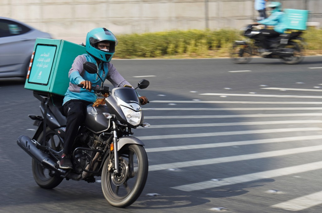 A delivery driver for the app Deliveroo speeds through a roundabout, in Dubai, United Arab Emirates, Thursday, Sept. 9, 2021. Advocates and workers sa...