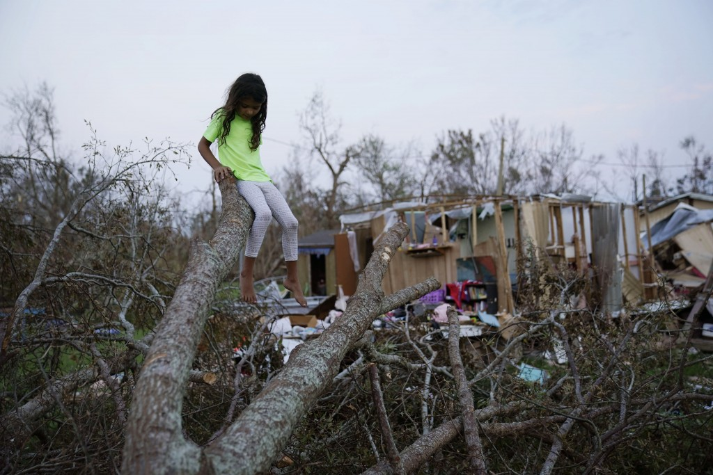 FILE - In this Sept. 4, 2021 file photo, six-year-old Mary-Louise Lacobon sits on a fallen tree beside the remnants of her family's home destroyed by ...