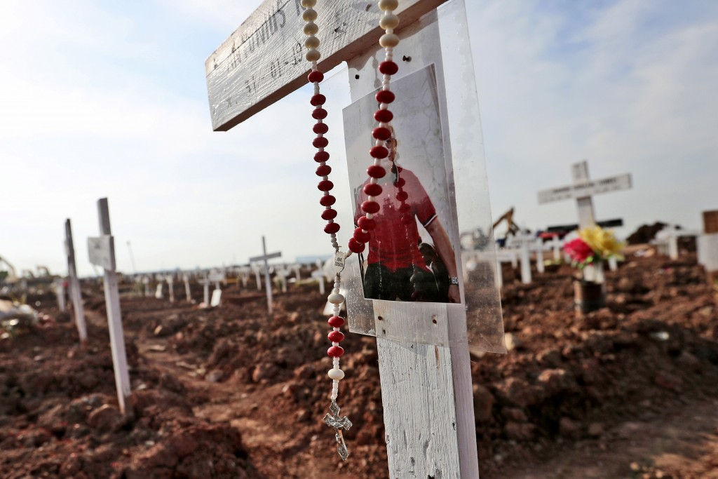 A rosary and a photograph are left at the grave of a man who died of COVID-19 at Rorotan Cemetery in Jakarta, Indonesia, Wednesday, Sept. 1, 2021. In ...