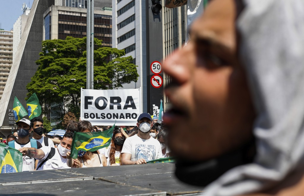"""Demonstrators hold a sign in Portuguese that reads """"Bolsonaro out,"""" during a protest against Brazilian President Jair Bolsonaro, at Paulista Avenue, S..."""