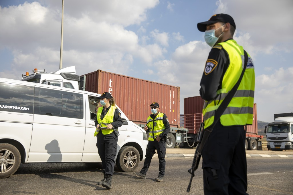 Israeli police check cars with Palestinian laborers as they search for two Palestinians who broke out of a maximum-security prison last week, on a roa...