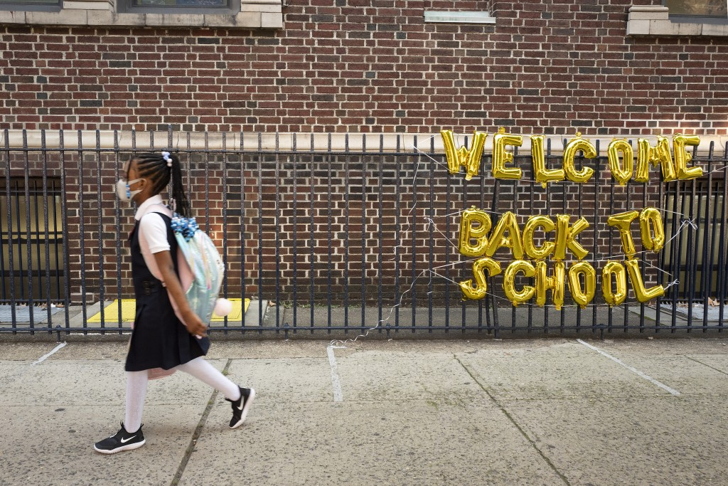 """A girl passes a """"Welcome Back to School"""" sign as she arrives for the first day of class at Brooklyn's PS 245 elementary school, Monday, Sept. 13, 2021..."""