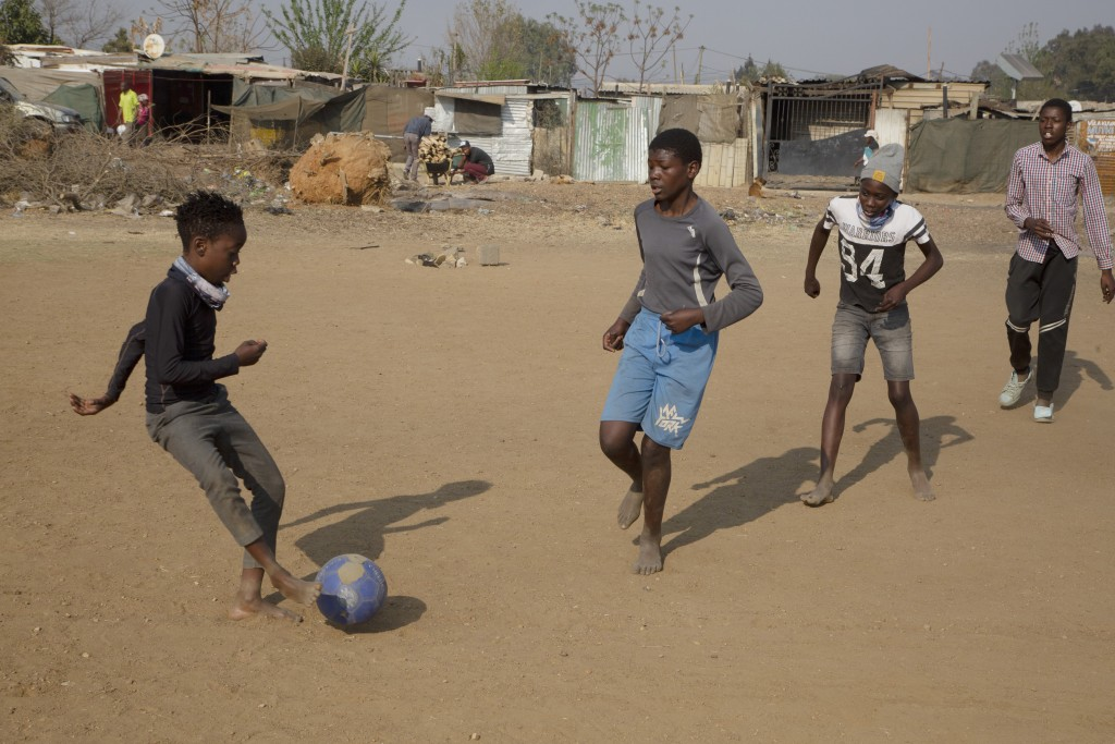 Children play on a dusty field outside their homes in the Diepsloot Township north of Johannesburg, Thursday Aug. 26, 2021. After uncertainty over whe...