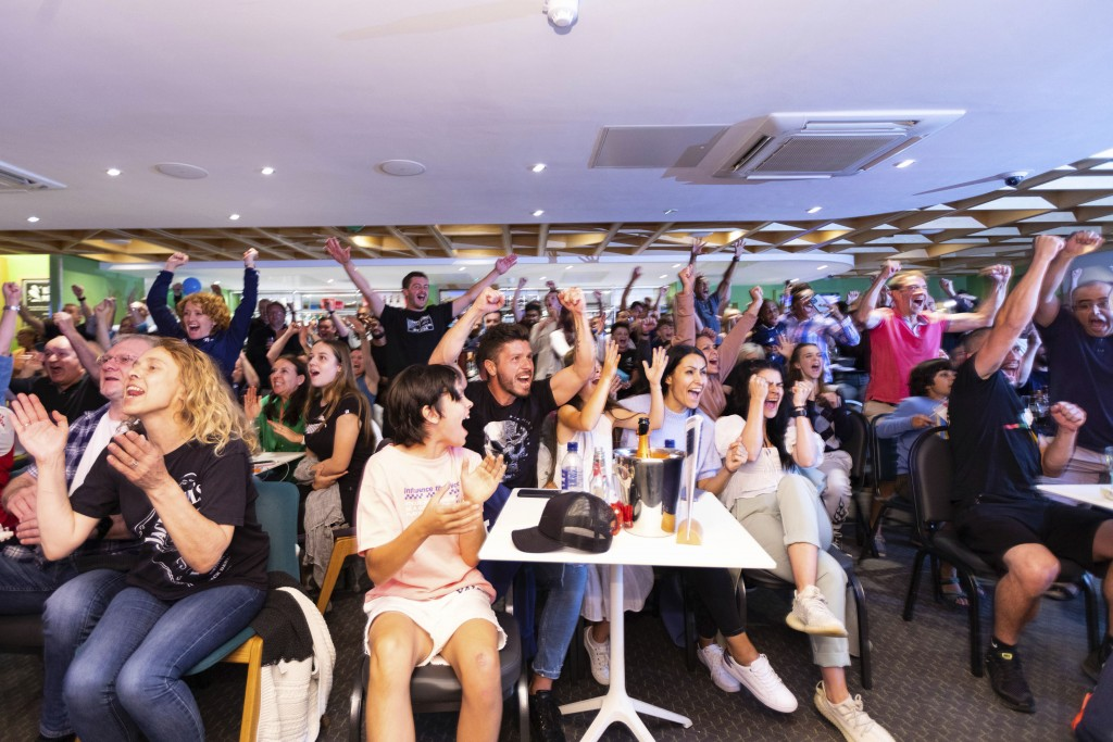 People watching remotely celebrate after British teenager Emma Raducanu beat Canadian teenager Leylah Fernandez in the U.S. Open final at The Parklang...
